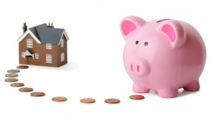 29117532 - piggy bank following money to a house isolated on a white background