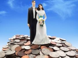 33705255 - plastic wedding couple on coins - money concept