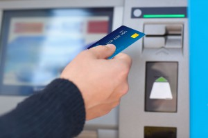 33954782 - man hand puts credit card into atm