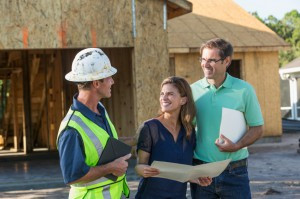 Builder and couple at new home under construction