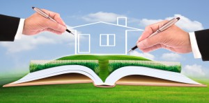 business man writing new house on beautiful green field use for multipurpose