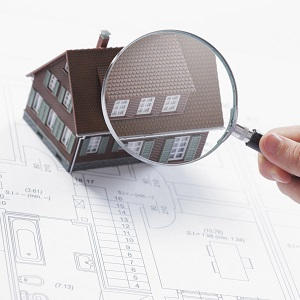 Concept image of a home inspection. A male hand holds a magnifying glass over a miniature house.